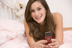 Jugendliche, die auf ihrem Bett unter Verwendung des Handys liegt Lizenzfreie Stockbilder