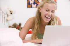 Jugendliche, die auf ihrem Bett unter Verwendung des Laptops liegt stockfotografie
