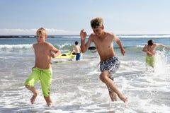 Jugendliche, die auf Strand spielen Lizenzfreie Stockfotografie