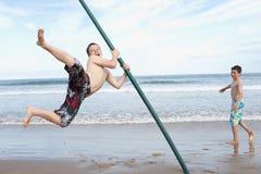 Jugendliche, die auf Strand spielen Lizenzfreie Stockbilder