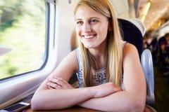 Jugendliche, die auf Zug-Reise sich entspannt lizenzfreies stockfoto