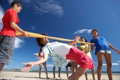 Jugendliche, die Überhangstanz auf Strand tun Stockbild