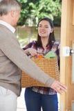Jugendliche, die das Einkaufen für älteren Nachbar tut Stockfotos