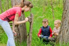 Jugendliche, die das Spielen mit zwei Jungen aufpasst stockbild