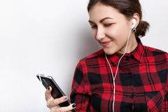 Jugendliche, die das stilvolle überprüfte Hemd hört ihre Lieblingsmusik mit dem lächelnden Schauen der Kopfhörer in den Schirm tr lizenzfreies stockbild