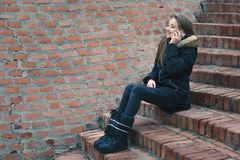 Jugendliche, die draußen auf dem Smartphone spricht Stockbilder