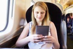 Jugendliche, die ein Buch auf Zug-Reise liest lizenzfreie stockbilder