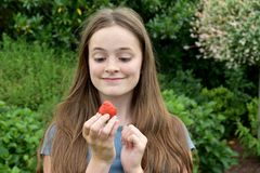 Jugendliche, die eine Erdbeere isst lizenzfreie stockfotografie