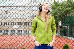 Jugendliche, die an einem Maschendrahtzaun sich lehnt Lizenzfreie Stockbilder
