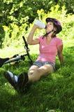 Jugendliche, die in einem Park mit einem Fahrrad stillsteht Lizenzfreie Stockfotografie