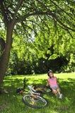 Jugendliche, die in einem Park mit ihrem Fahrrad sich entspannt Stockbilder