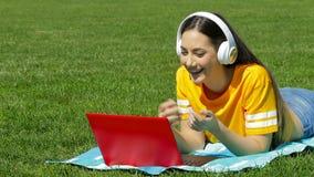 Jugendliche, die einen Videoanruf mit einem Laptop auf dem Gras hat stock video footage