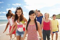 Jugendliche, die entlang dem Strand spazierengehen Stockfotos