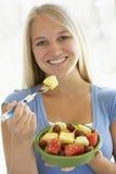 Jugendliche, die frischen Fruchtsalat isst Stockbild