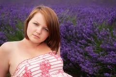 Jugendliche, die gegen Lavendelfeld aufwirft Lizenzfreie Stockbilder