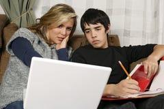 Jugendliche, die Heimarbeit mit Laptop tun stockbilder