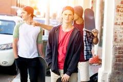 Jugendliche, die hinunter die Straße am Sommertag gehen Lizenzfreies Stockbild
