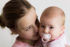 Jugendliche, die ihr kleines kleines Schwesterchen In Her Arms hält Stockbild