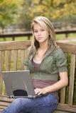 Jugendliche, die ihren Laptop im Park verwendet Stockfoto