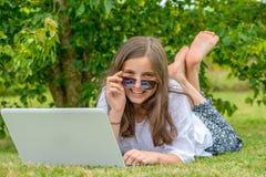 Jugendliche, die im Gras unter Verwendung des Laptops liegt lizenzfreie stockfotos