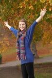 Jugendliche, die im Herbst-Park mit den Armen heraus steht Stockbilder