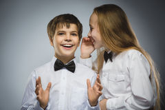 Jugendliche, die im Ohr von jugendlich Jungen auf einem grauen Hintergrund flüstert Positives menschliches Gefühl, Gesichtsausdru stockfotos