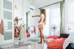 Jugendliche, die Kleidung im Wandschrank wählt stockbild