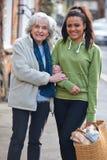 Jugendliche, die älterer Frau Carry Shopping hilft Stockbild