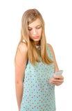 Jugendliche, die mit einem Telefon in seiner Hand steht stockfotografie