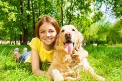 Jugendliche, die mit ihrem Schoßhund im Park legt Lizenzfreie Stockfotos