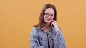 Jugendliche, die nett auf einem gelben Hintergrund lächelt und schaut stock video footage