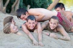 Jugendliche, die Spaß auf dem sandigen Strand haben Stockfotografie