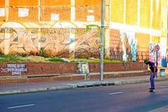 Jugendliche, die in die Straße von Johannesburg-Stadt Skateboard fahren Stockbilder