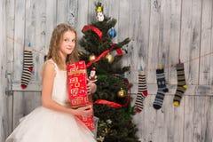 Jugendliche, die Weihnachtsgeschenk vor Baum des neuen Jahres hält Stockbild