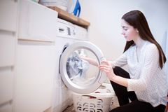Jugendliche, die zu Hause bei den inländischen Aufgaben leeren Waschmaschine hilft lizenzfreie stockfotografie