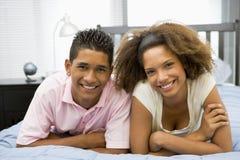Jugendliche, die zusammen auf Bett liegen Stockfoto