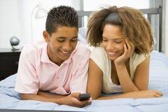 Jugendliche, die zusammen auf Bett liegen Lizenzfreies Stockfoto