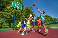 Jugendliche, die zusammen Basketballspiel spielen stockbild