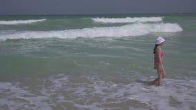 Jugendliche in einem Badeanzug springt glücklich in die Wellen des Persischen Golfs auf Strand des Dubai-Vorratgesamtlängenvideos stock video