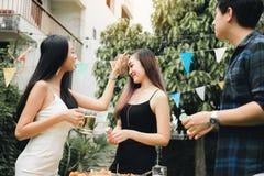 Jugendliche genie?en ein Gartenfest zu Hause und halten das Bierglas in der Hand lizenzfreie stockbilder