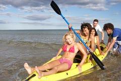 Jugendliche im Kanu im Meer lizenzfreie stockbilder