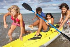 Jugendliche im Meer mit Kanu stockfotografie