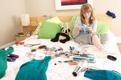 Jugendliche im unordentlichen Schlafzimmer, das Fahrwerkbeine einwächst Stockfotografie