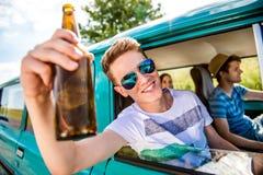Jugendliche innerhalb eines alten campervan, trinkenden Bieres, roadtrip lizenzfreie stockfotos