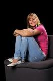 Jugendliche-lächelndes Sitzen auf Stuhl lizenzfreie stockfotos
