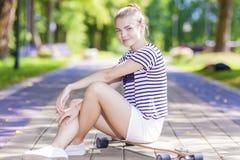 Jugendliche Lebensstil, Konzepte und Ideen Positives blondes kaukasisches Mädchen, das mit Longboard im Park aufwirft Lizenzfreie Stockbilder