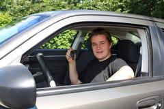 Jugendliche männliche darstellende Autotaste hinter dem Rad Stockbild