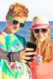 Jugendliche machen Selbstporträt und hörende hörende Musik auf dem Seehintergrund Lizenzfreies Stockbild