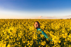 Jugendliche mit dem langen Haar auf dem gelben Bittercressgebiet Stockfotografie