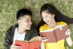Jugendliche mit den Büchern, die auf grünem Gras liegen stockfotografie